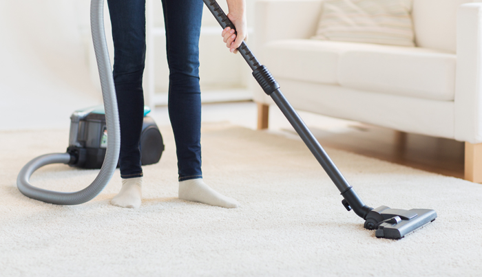 Superior close up of woman legs with vacuum cleaner at home in cleveland