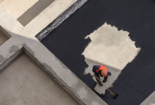 person applying roof coating with brush roller