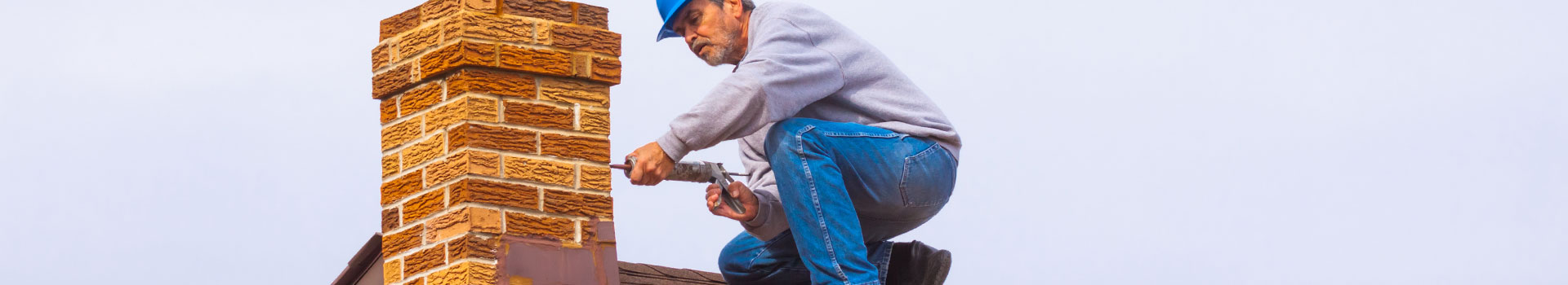 man sealing chimney with caulking gun