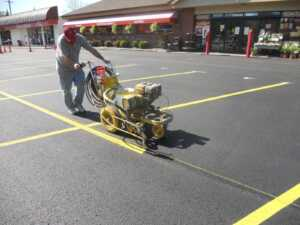 Image of employee painting stripes on parking lot with machine